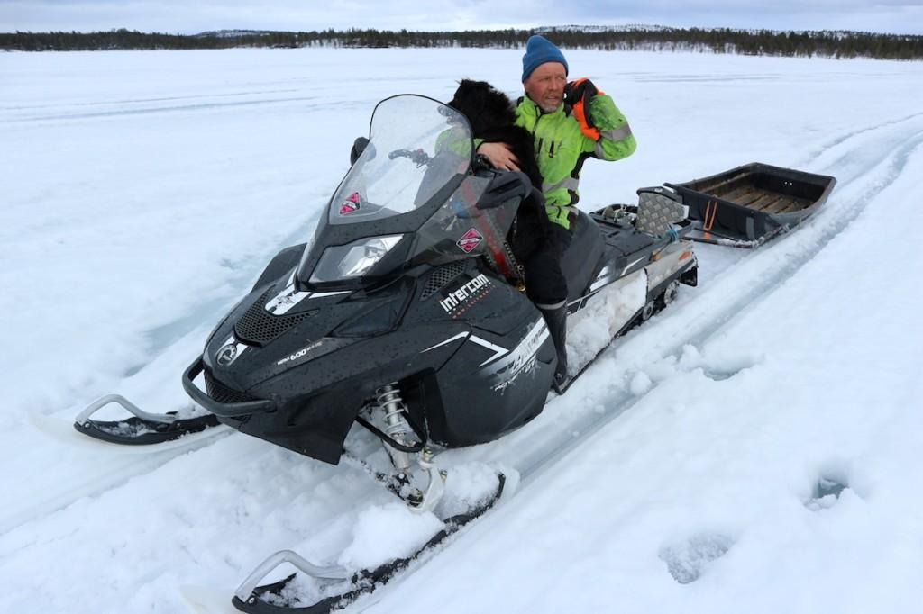 Juha Feodoroff on lake Kirakkajärvi ice with his dog, after a long day at restoration work.